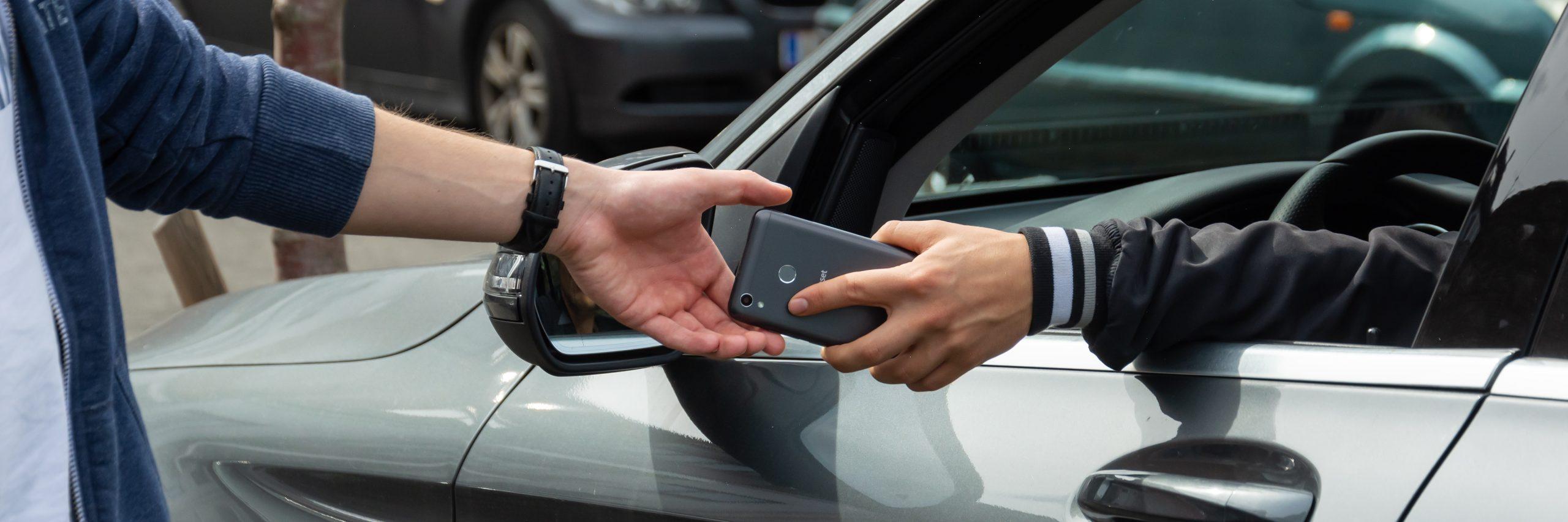 Handy Übergabe am Auto; Hände; Handy; Smartphone; P2P-Sharing; Peer to Peer Sharing