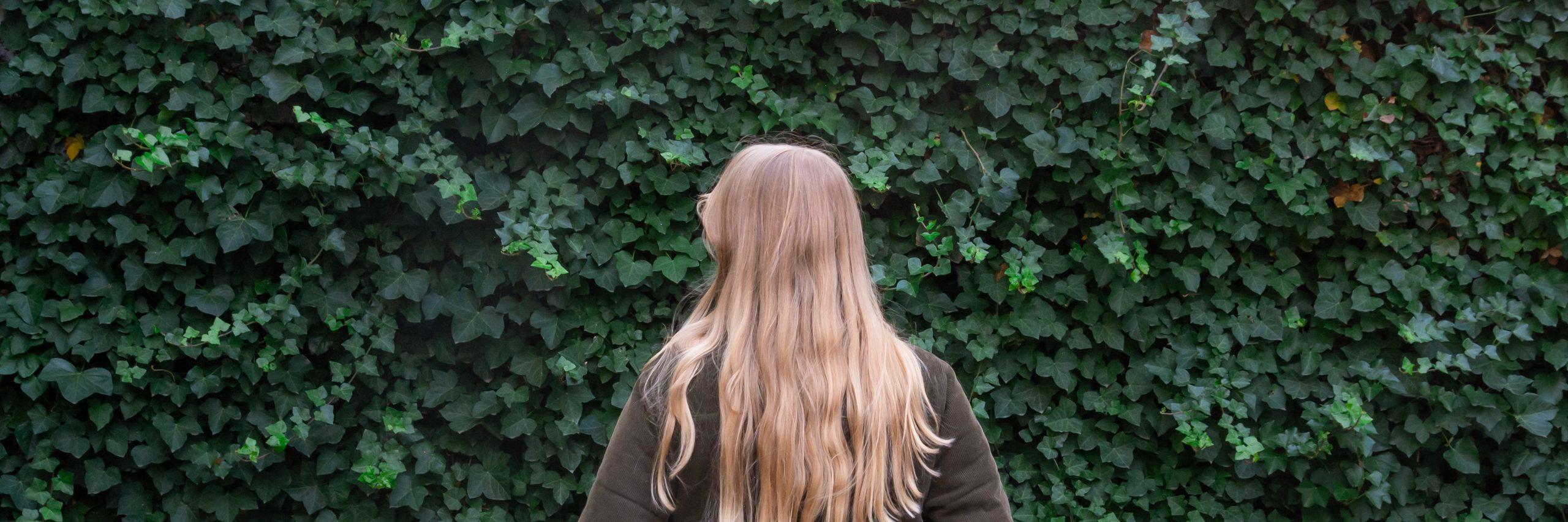 Mädchen vor grüner Hecke